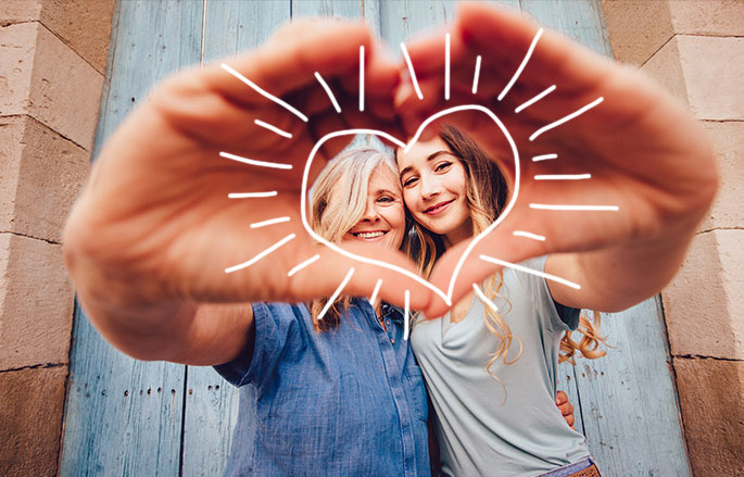 teenager with mother using hands to make a heart shape towards camera