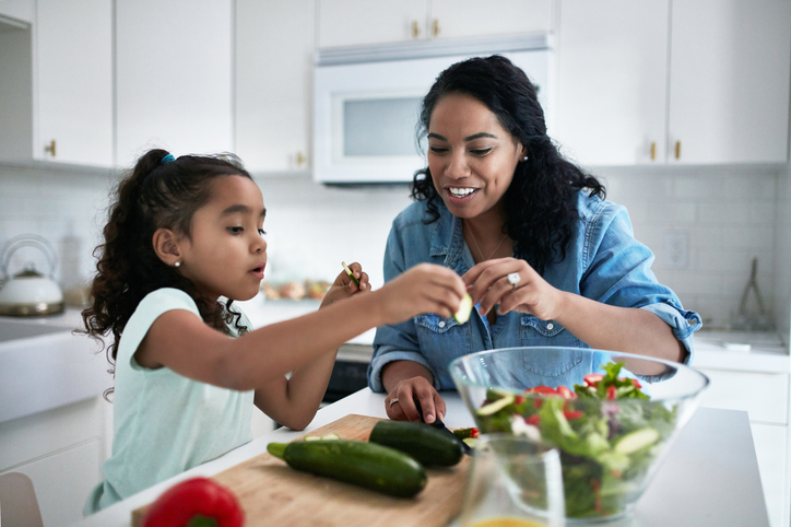 a mom and her daughter making a salad in a large glass bowl. They are cutting up cucumbers and putting them in the bowl