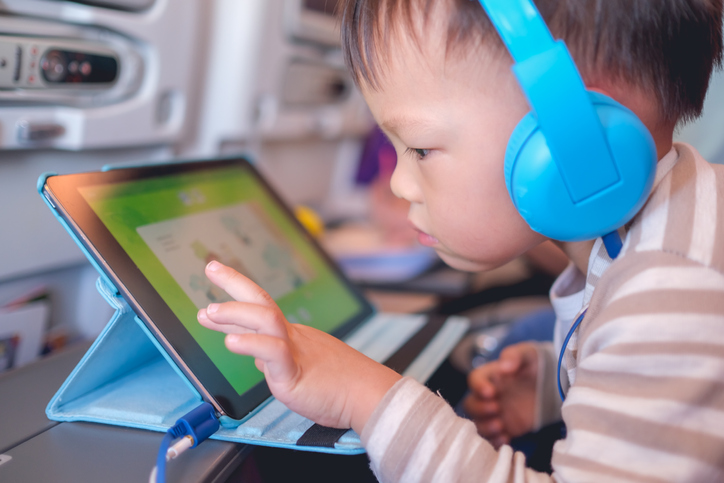 Picture of an asian baby on an airplane playing with a table and headphones on