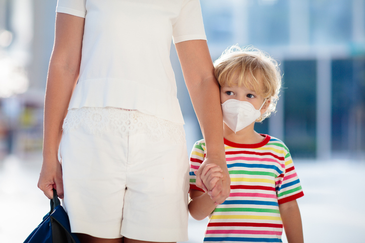 Picture of a mom holding hands with her son wearing a rainbow shirt wearing a mask on his face