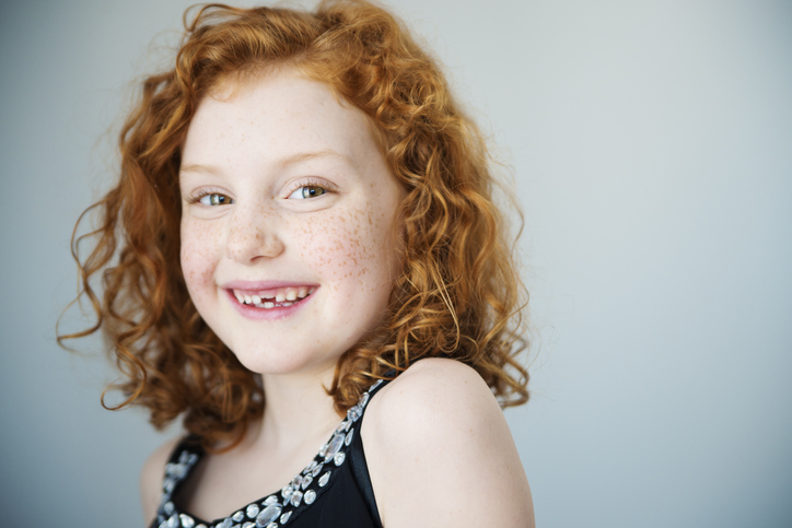 picture of a red headed girl smiling at the camera in front of a light blue background
