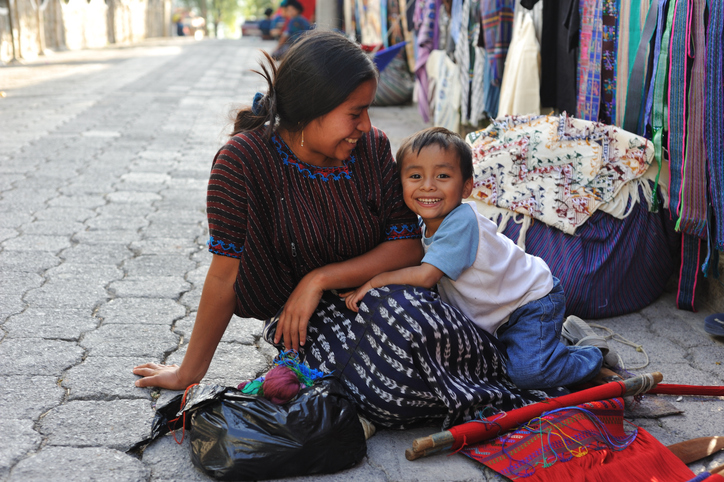 A picture of a mother and child sitting on the street at a bazaar