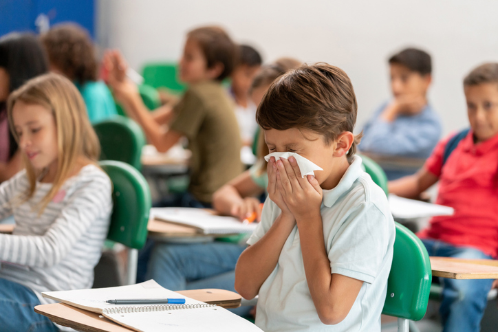 a boy sneezing into a tissue at school