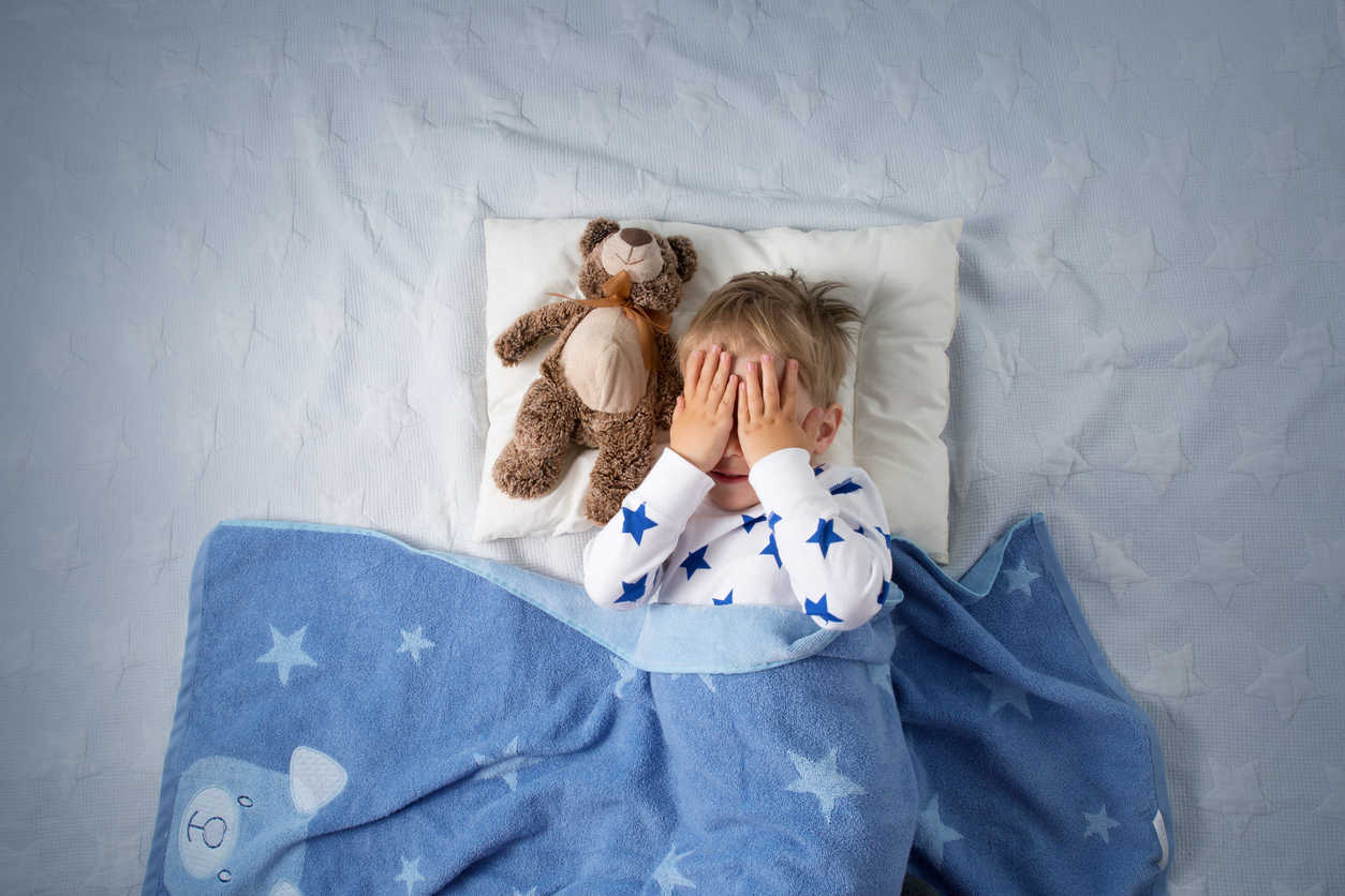three year old boy laying in bed with a blanket and a teddy bear looking scared