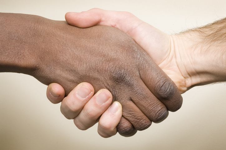 white hand shaking hand of a black man