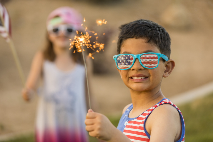 young boy in american flag sunglasses holding a sparkler