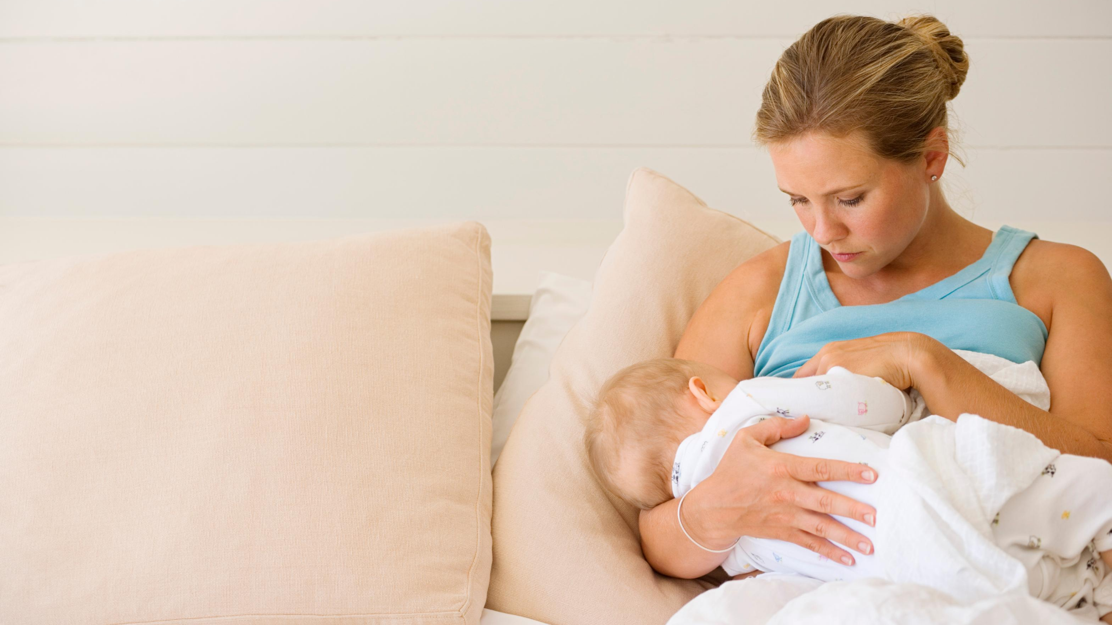 a mom breastfeeding a baby on the couch