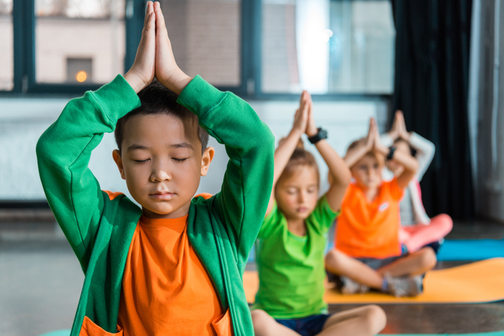 children doing meditative younger on yoga mats