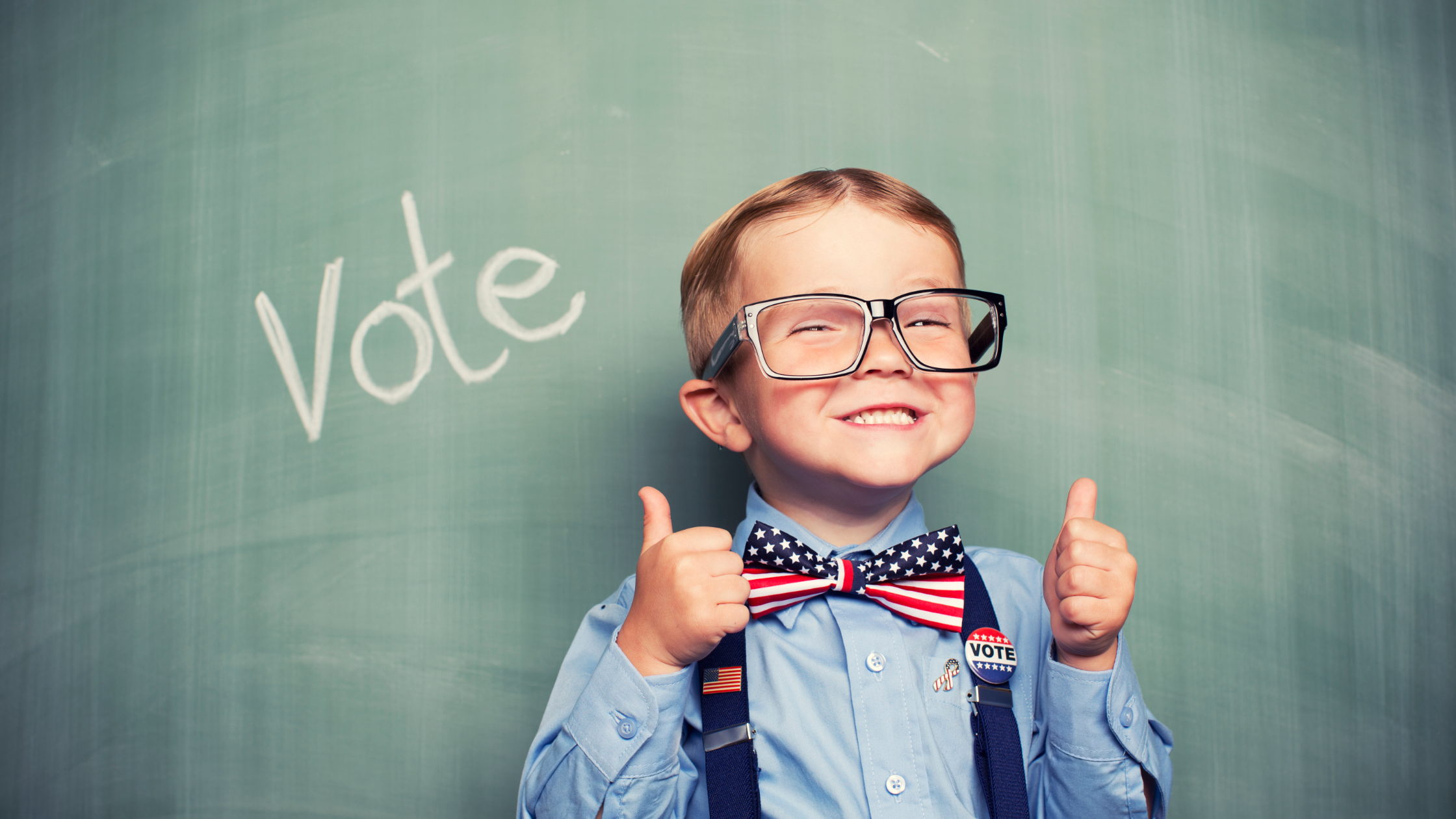 young boy standing in front of a blackboard with the work vote written
