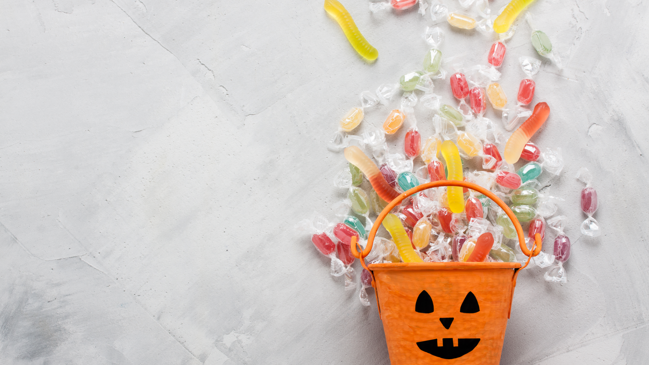 pumpkin decorated candy bucket with candy flowing out