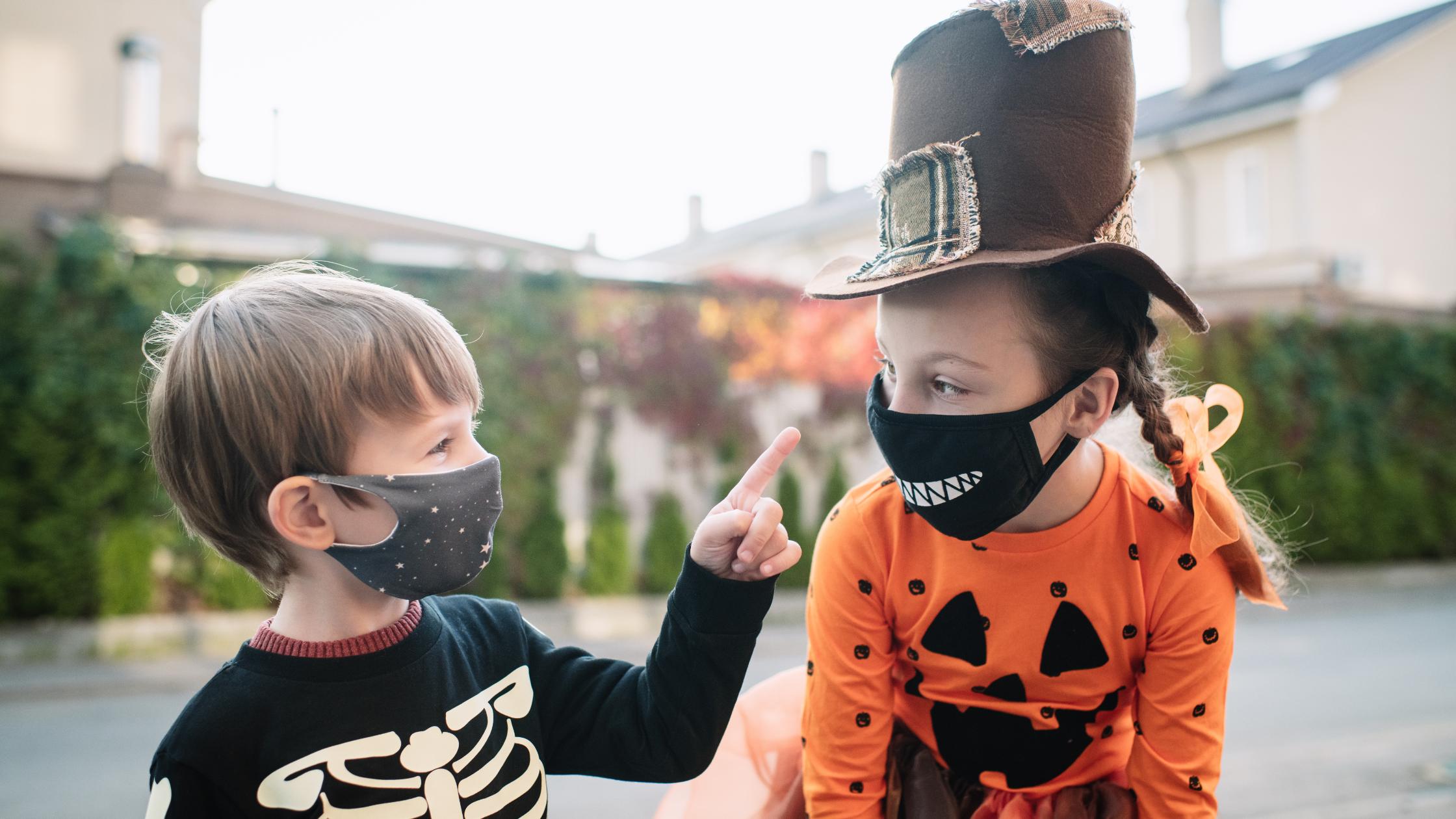 boy in skeleton shirt pointing at girl in pumpkin shirt